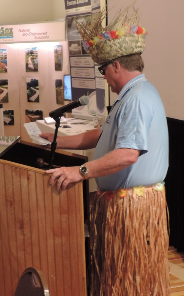 Man talking from behind podium with a Hawaiian skirt and hat on
