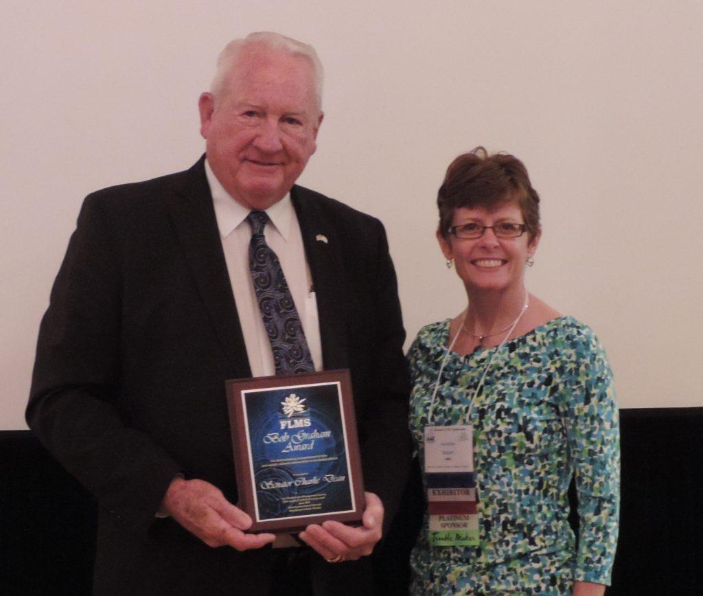 Man holding award next to woman smiling
