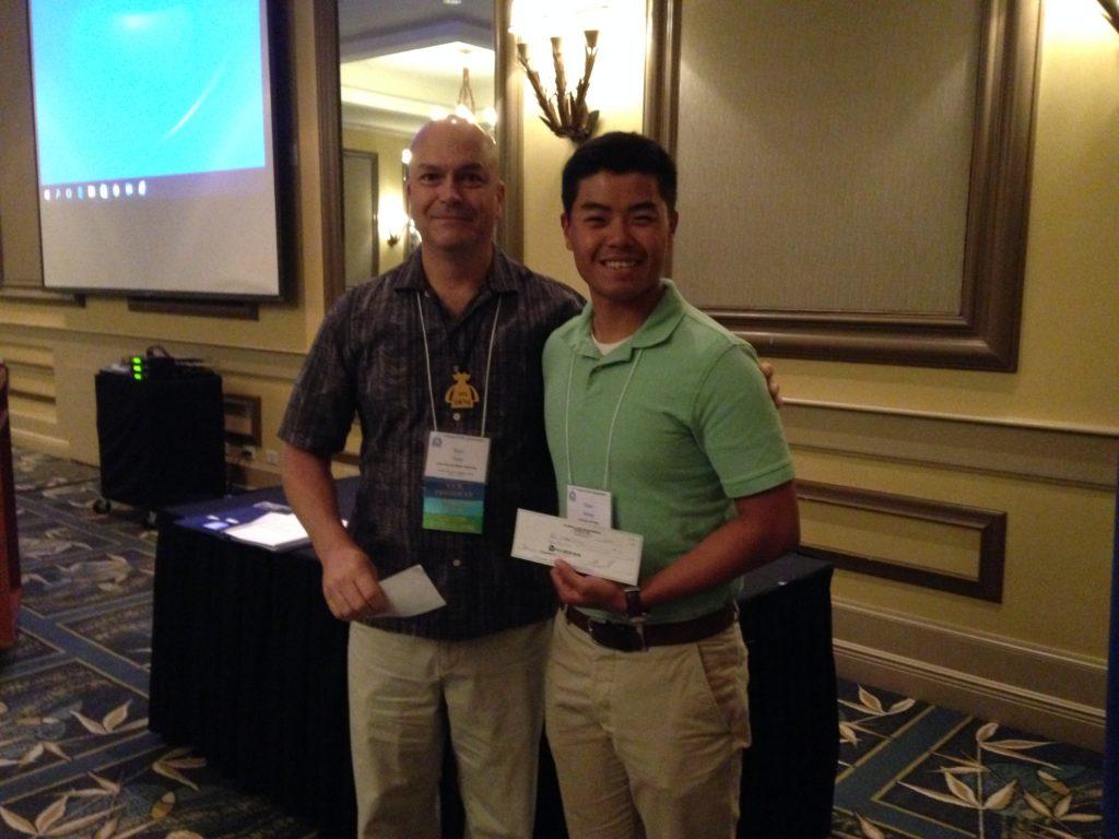 2 people smiling holding awards.